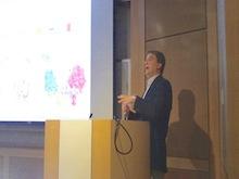 Dr. Lee Kraus speaking at a podium.