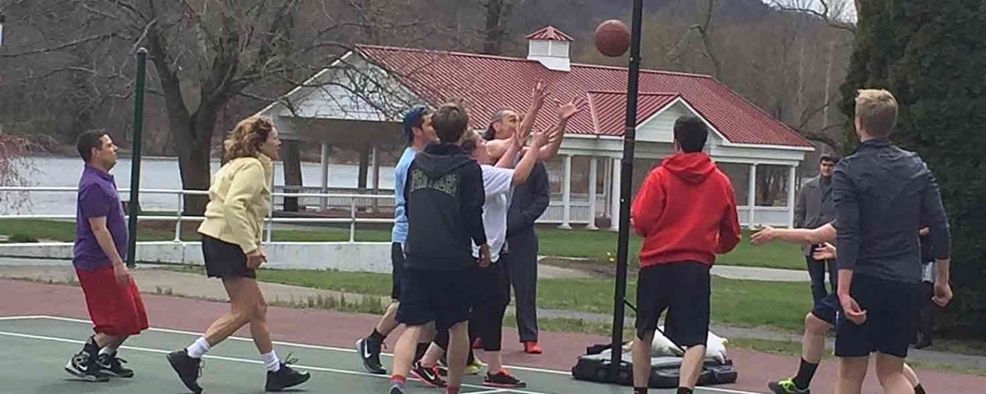 Group playing basketball outside.