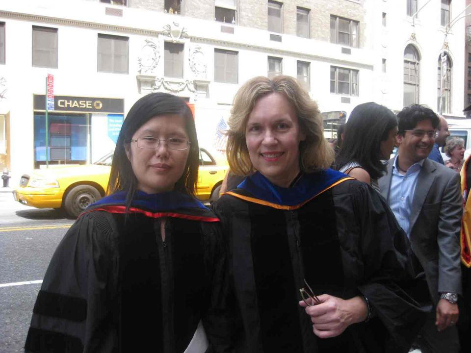 Dr. Gudas standing with graduate outside.
