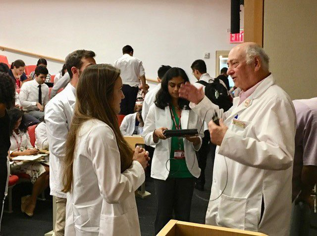 Students wearing lab coats talk with professor.