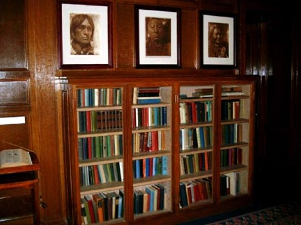 Portraits hang above bookcase.
