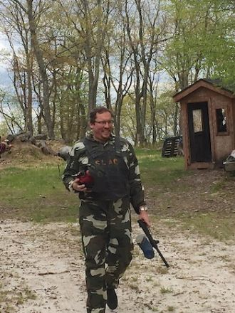 Man in forest playing paintball.