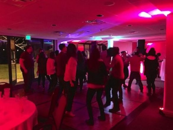 Pink lit party of students dancing.