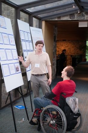 Man in wheelchair reading a presentation board.