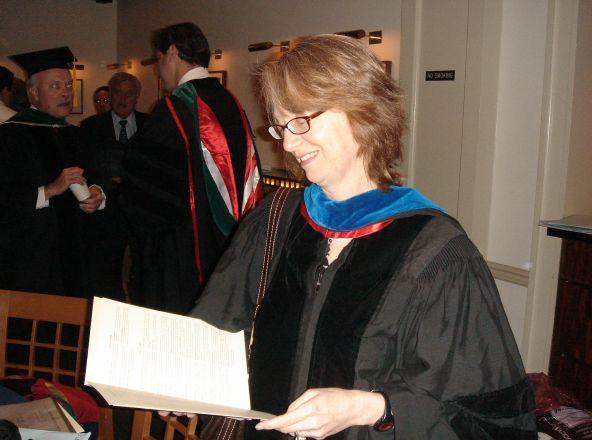 Woman in regalia reading a paper.