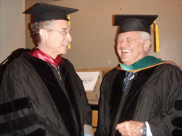 Professors in regalia laughing.